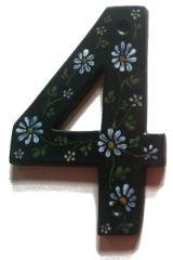 husnummeret 4: sort glasur med almueinspireret bemaling i hvid, gul og lysegrøn